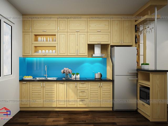 Mẫu tủ bếp cho phòng bếp nhỏ được thiết kế kèm quầy bả mini bằng chất liệu gỗ sồi nga tự nhiên màu sắc vàng sáng trẻ trung kết hợp kính cường lực màu xanh dương cực kì mát mắt