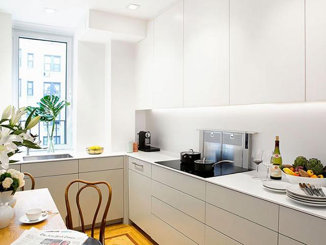 Nhà bếp hình vuông được thiết kế với tone màu trắng tinh tế. Thiết kế tận dụng tối đa diện tích nhưng vẫn chưa lại khoảng di chuyển thuận tiện