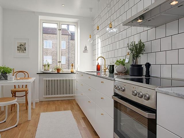 Mẫu nhà bếp hình vuông được thiết kế dành cho nhà chung cư với màu trắng chủ đạo tinh tế tạo cảm giác phòng bếp như rộng rãi hơn nhiều