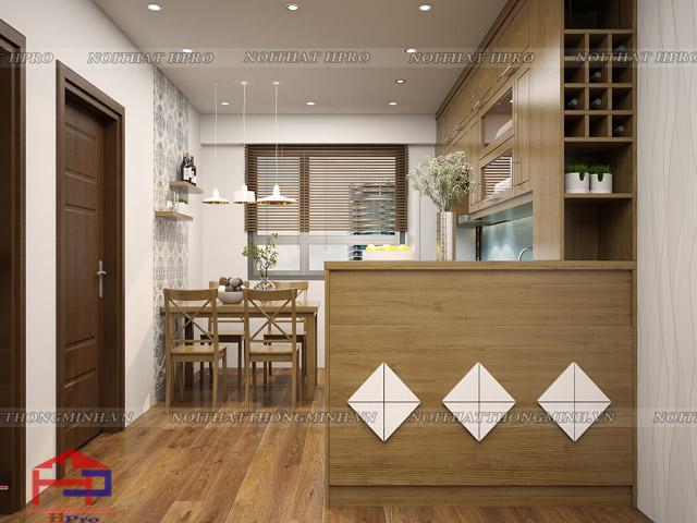 Chất liệu gỗ sồi mỹ tự nhiên được sử dụng cho không gian nhà bếp hình vuông này tạo nên sự ấm cúng. Sự hiện đại từ những đường nét mặt cánh tủ và quầy bar mini kết hợp tủ rượu ấn tượng